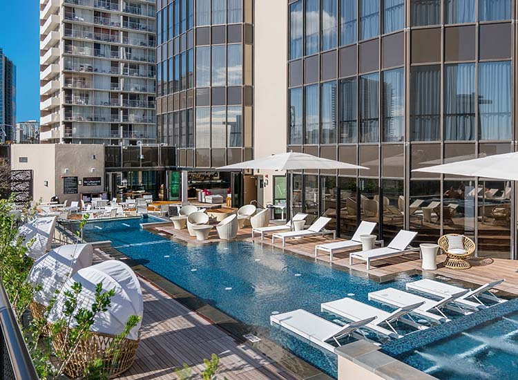 The property's deck features a wading pool and plenty of seating as well as tables for alfresco dining. // © 2017 Hyatt Centric Waikiki Beach