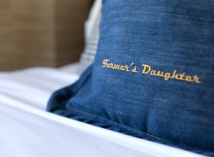 Guestrooms showcase branded denim pillows. // © 2017 Farmer's Daughter Hotel