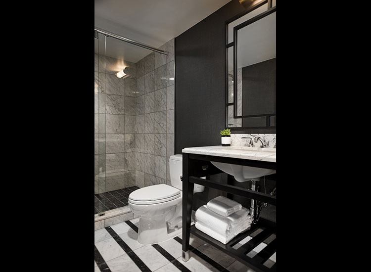 Bathrooms feature marble flooring and counters as well as  a large glass-enclosed rain shower. // © 2017 Kimpton Mason & Rook Hotel