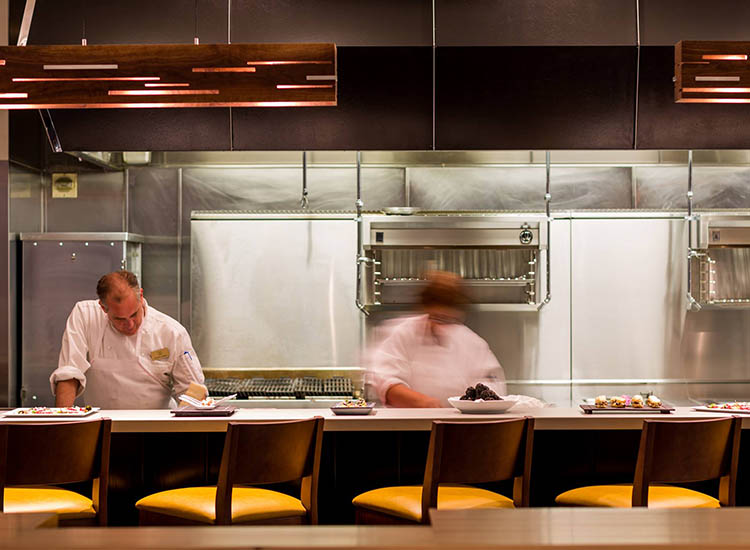 Diners near the open kitchen can watch as chefs masterfully whip up tasty dishes. // © 2017 Victor M. Samuel