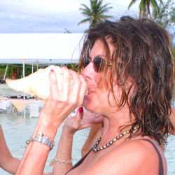 Gigi Becker blows on a conch shell during a motu picnic in Tahiti // © 2014 Gigi Becker